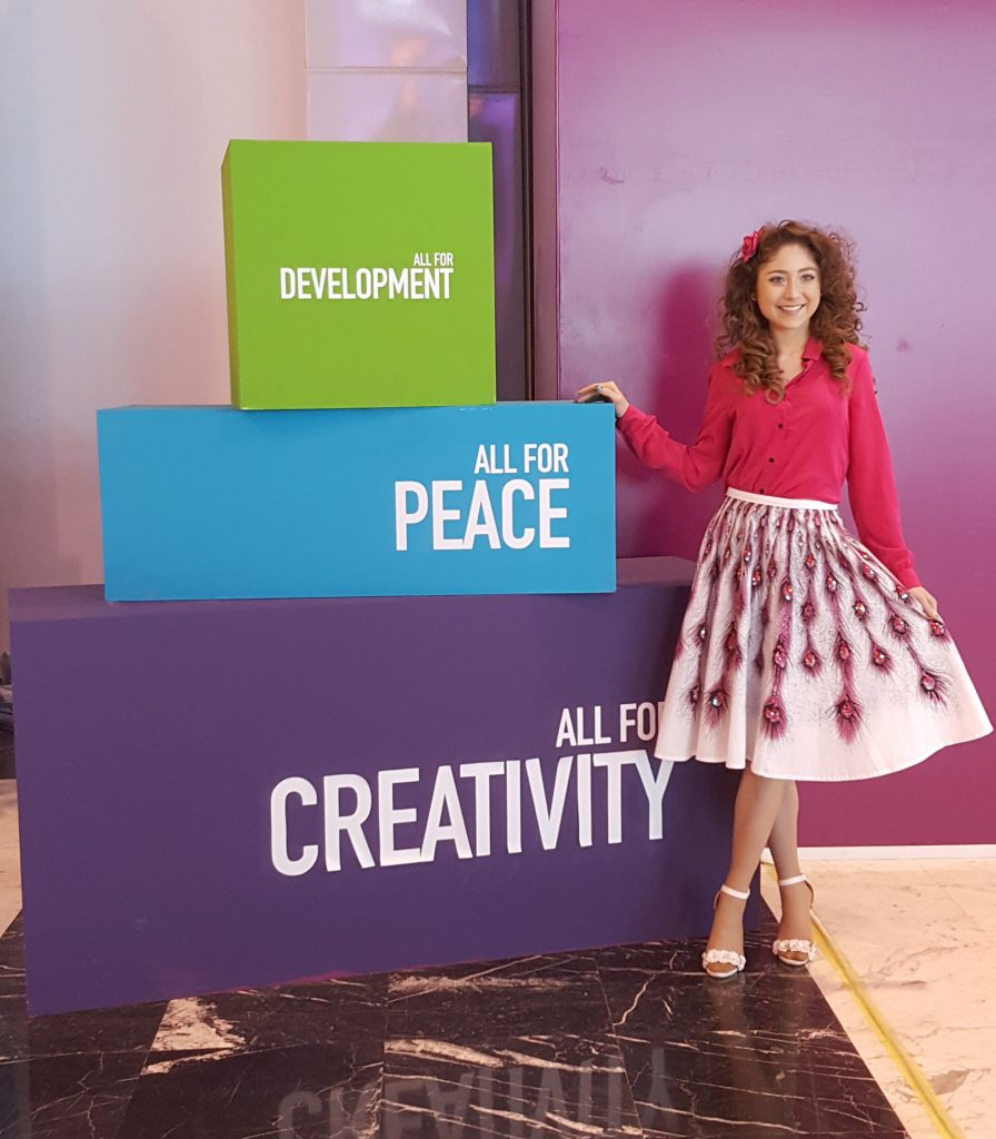 Kelly standing in front a colourful block tower made of three blocks reading all for development, peace and creativity