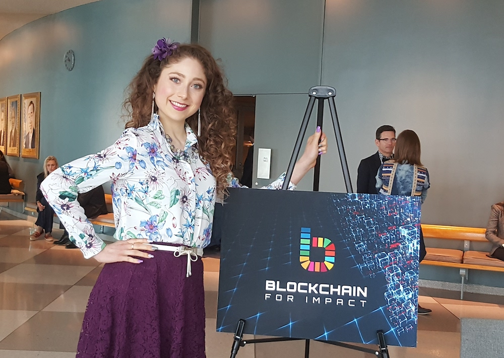Kelly in a floral blouse and purple skirt at the UN standing beside a Blockchain for Impact event sign