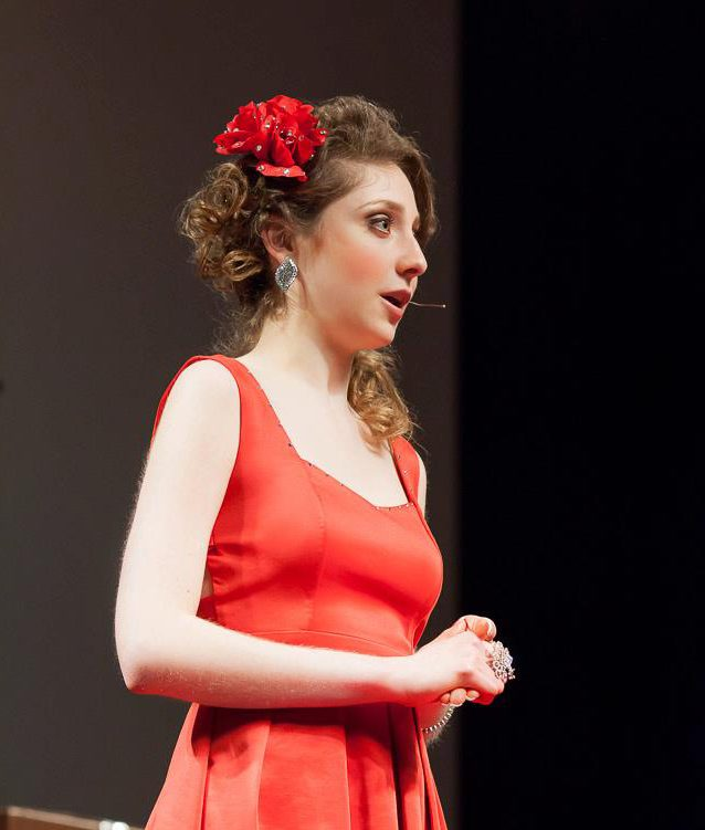 Kelly in a red dress on the TEDx stage