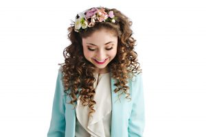 Kelly Lovell looking down with a big smile on her face and a vibrant coloured flowered headband