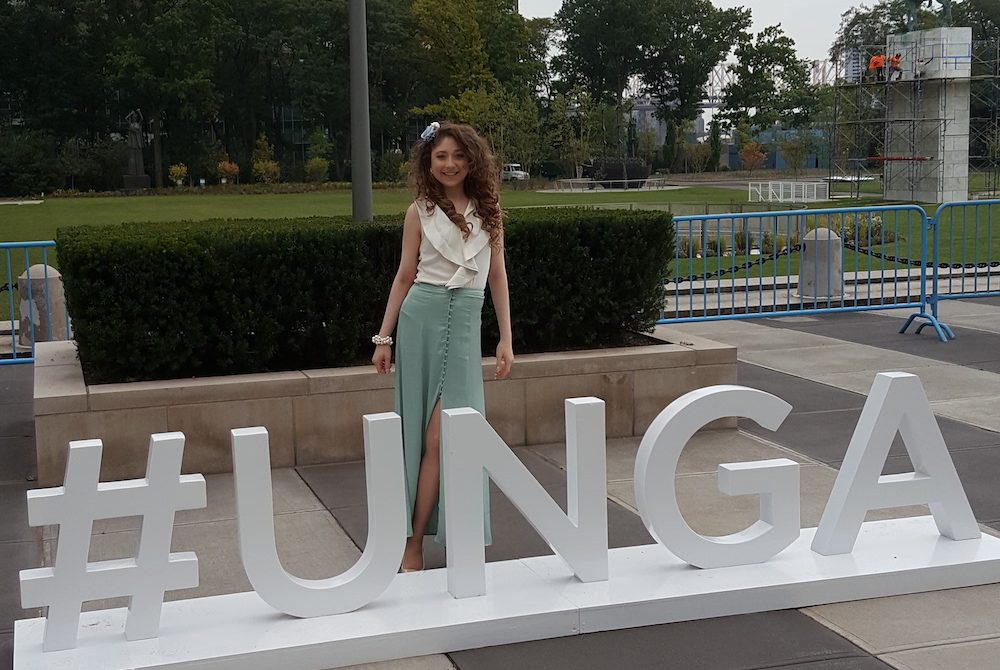 Kelly Lovell at the United Nations standing outside in front of #UNGA letters for the UN General Assembly