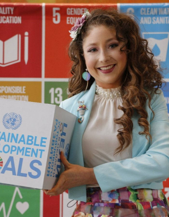 Kelly Lovell standing on stage at the United Nations with the colourful SDGs behind her as a backdrop