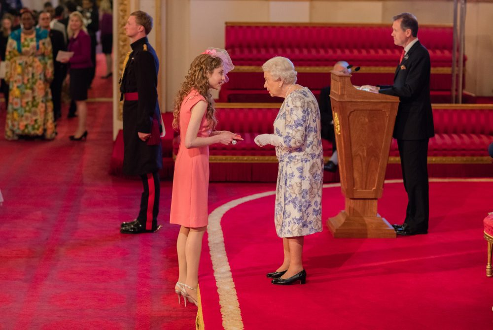 Kelly wearing a pink dress at Buckingham Palace shaking the Queen's hand as she is handed an award from Her Majesty in front of the Royal Family