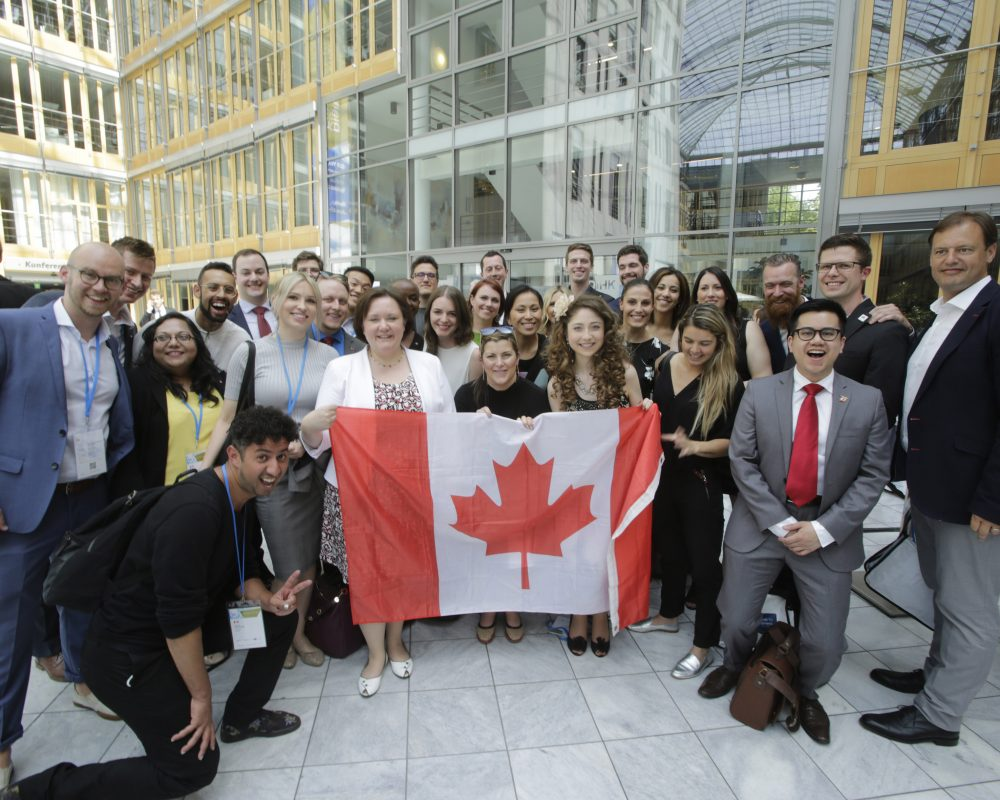 Kelly at the G20 Young Entrepreneurs' Alliance summit standing with a group of delegates holding the Canadian flag