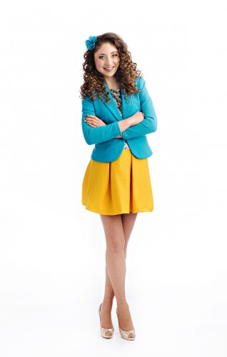 Kelly standing confidently with her arms crossed, wearing a blue blazer and yellow skirt