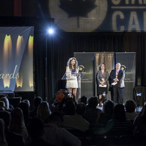 Kelly on staging holding up the Startup Canada Young Entrepreneur of the Year award