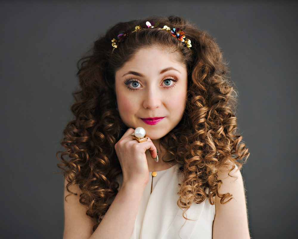 Kelly standing in a power pose wearing a white blouse, pink lipstick and curly long hair with a flower headband