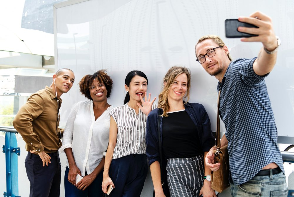 Millennial employees standing in a group taking a selfie