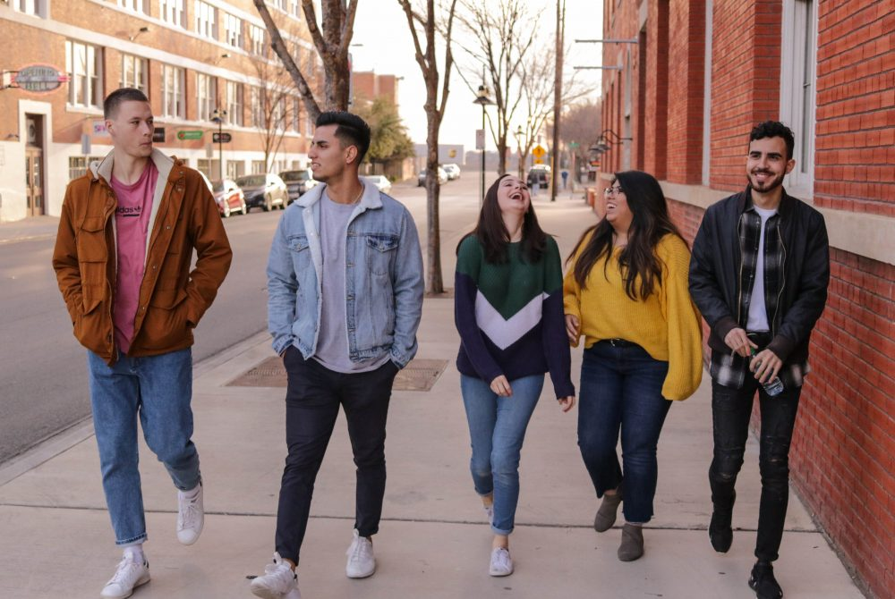 group of diverse Gen-Z youth walking together and smiling